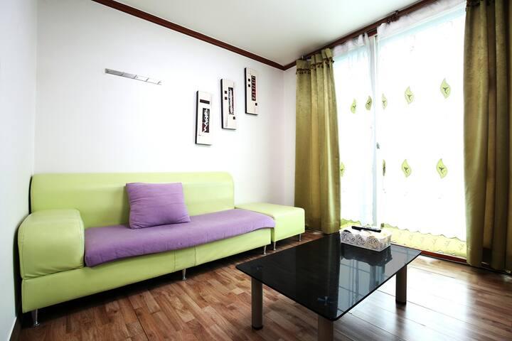 하늘하늘한 화이트 침실과 그린색 쇼파가 있는 화이트 객실