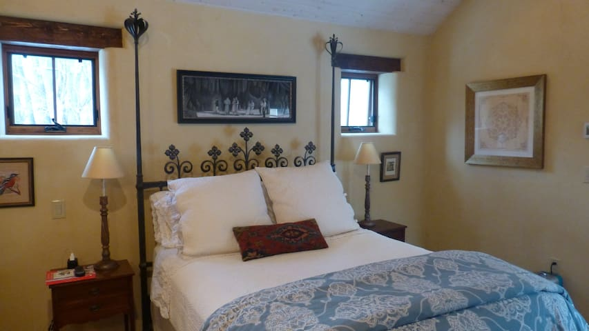 """the master bedroom features a queen-sized hand-forged iron bed with a super comfy """"hybrid"""" mattress"""