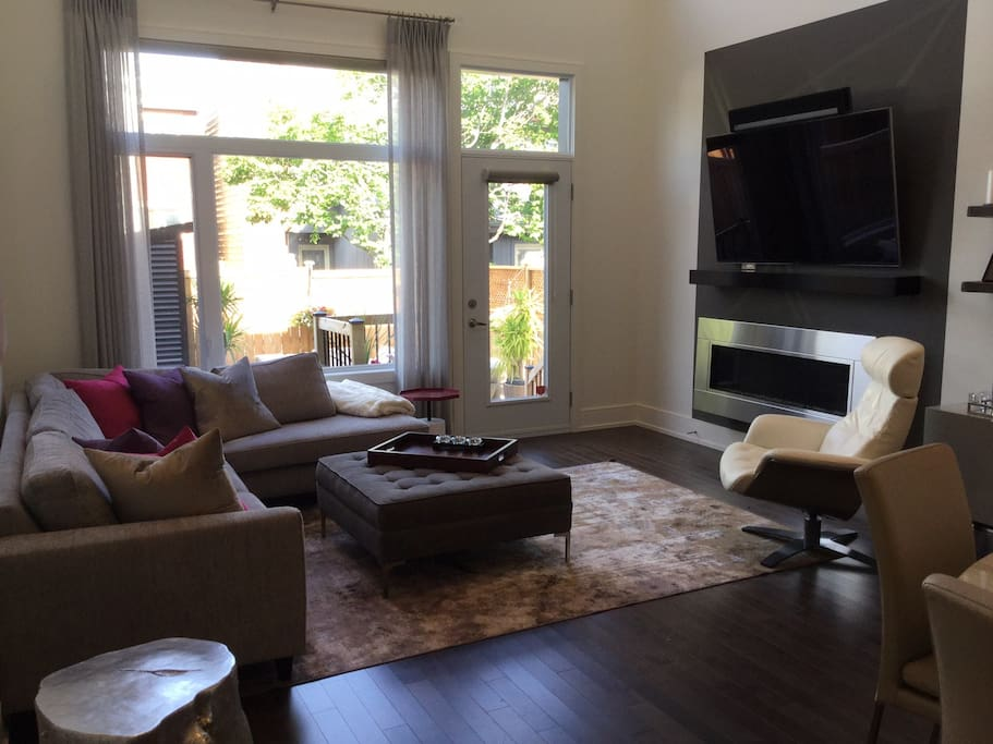 """Living room with gas fireplace and 65"""" wall mounted flat screen television"""