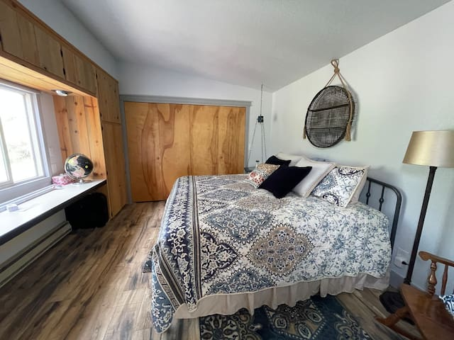Master bedroom with king size bed and clear view of river.  Box fan for warmer evenings.  Large built in wardrobes, large closet and dedicated work station.