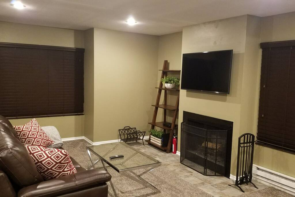 Living room with wood burning fireplace, couch and 50 inch TV with cable.