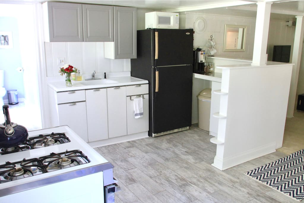 Kitchen with full size refrigerator, microwave, coffee pot (AND free trade coffee), and gas range/oven.