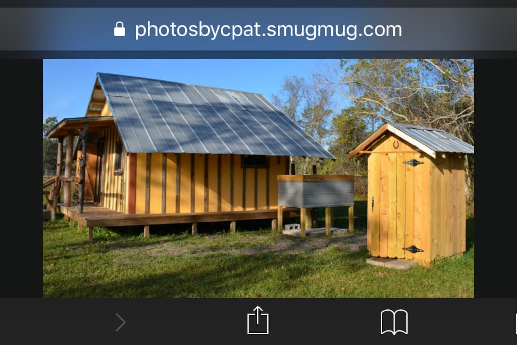 Hand built cabin, outdoor shower, and outhouse.
