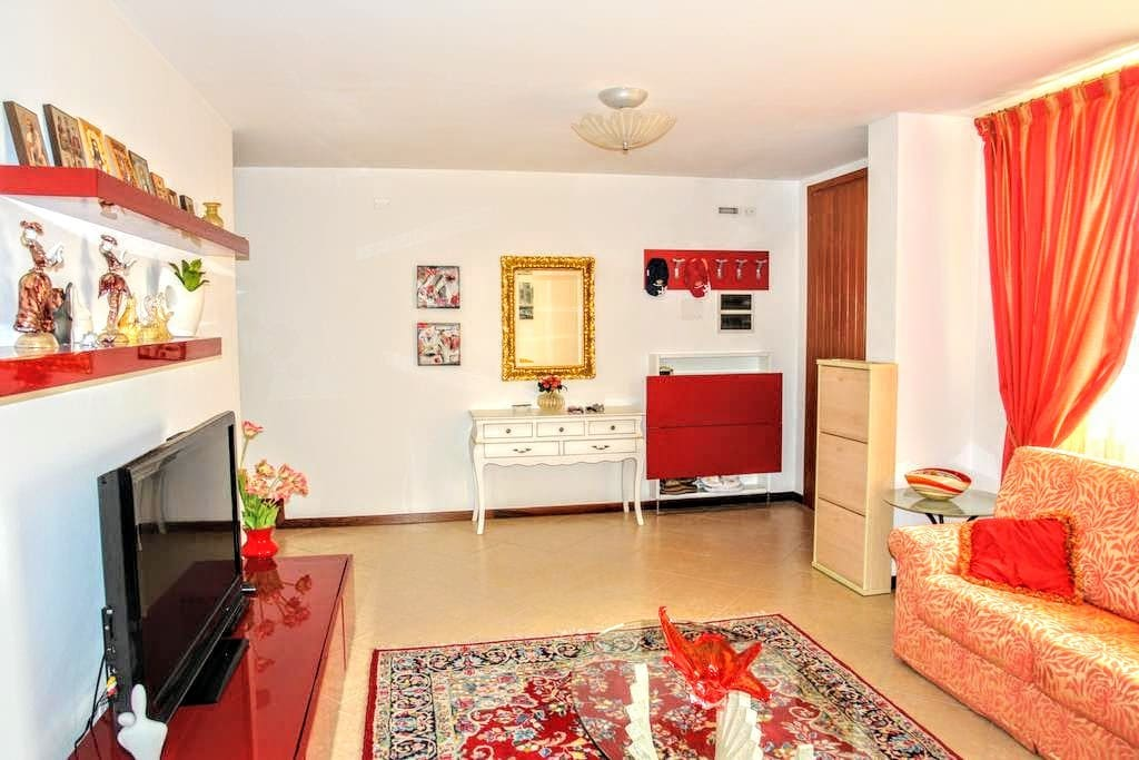 Enter in the living room with antique and modern furnitures with a comfortable sofa and satellite TV.