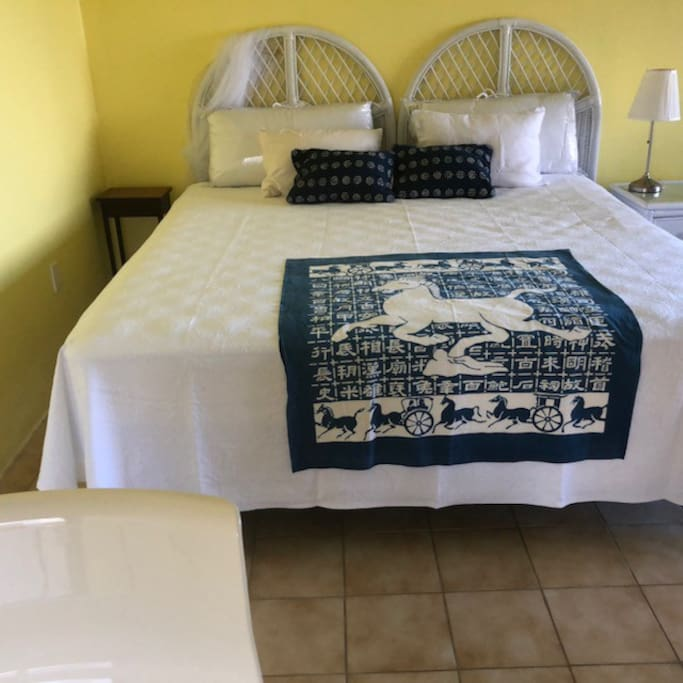 King-size bed with new pillows, sheets and covers. Water view from the bed, with covered deck outside.