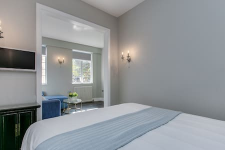 bedroom with doors for privacy and additional TV
