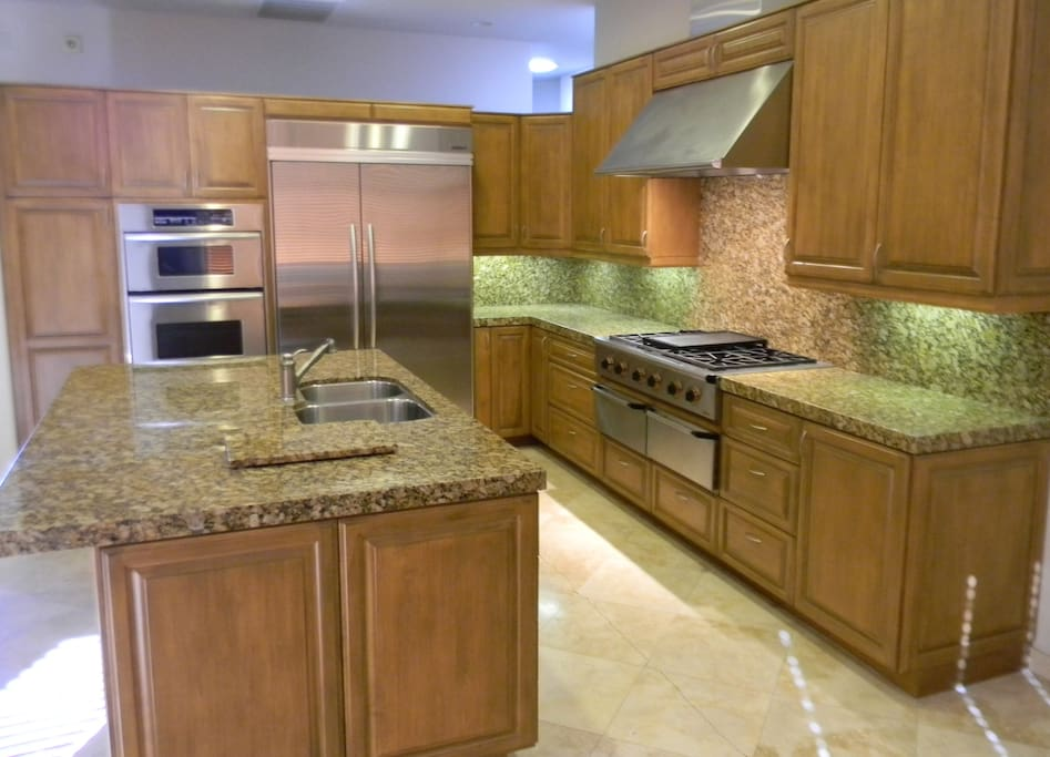 Gourmet kitchen with stainless steel appliances, granite countertops, 6 burner range and large island.
