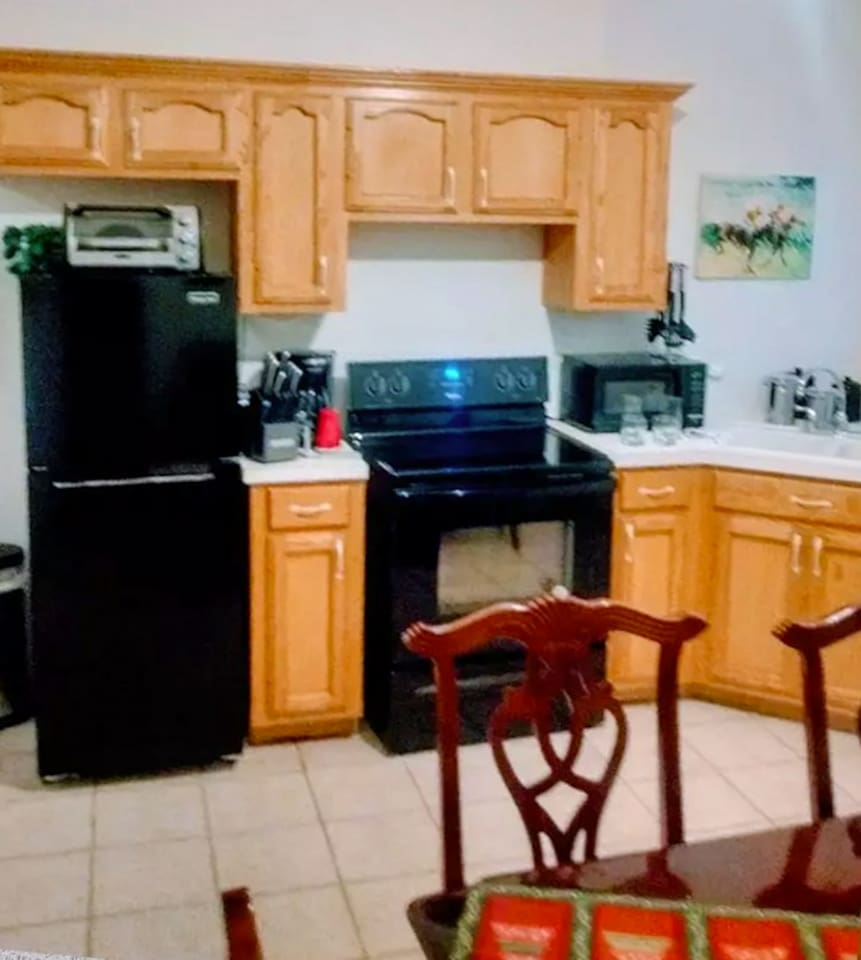 Fully furnished kitchen: stove/oven (electric), refrigerator, microwave, utensils, cookware, dish ware, coffee makers, and toaster oven.
