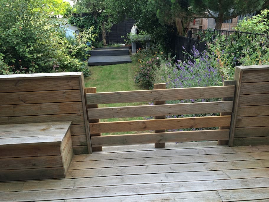 Large patio leading into large lawned garden, with a safety gate for children
