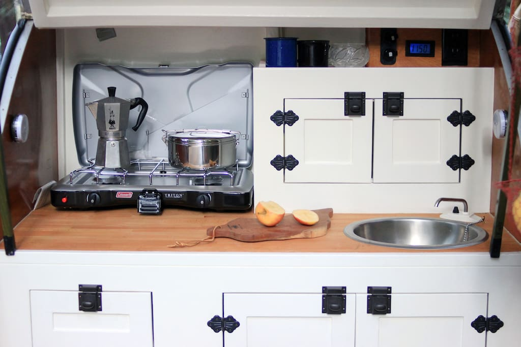 Our galley includes all the necessary amenities for you to cook a great meal. A brand new Triton two-burner stove, a cast-iron pan, a battery-powered sink, and all manner of utensils, plates, and other amenities. Yum!