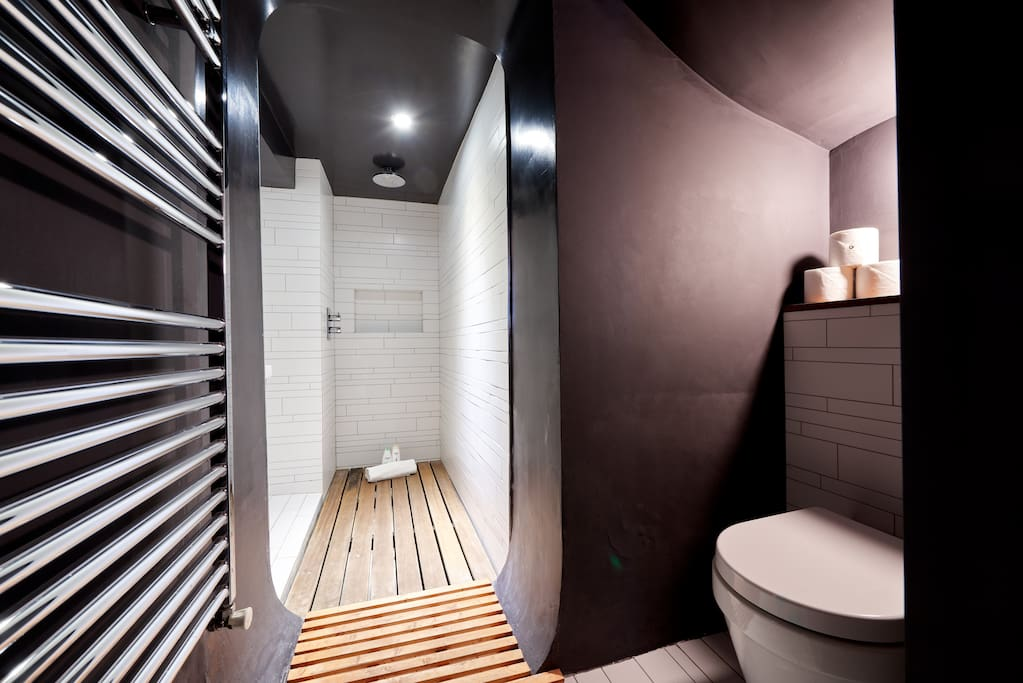 The contemporary bathroom benefits from a walk-in rain shower and wooden floor mats