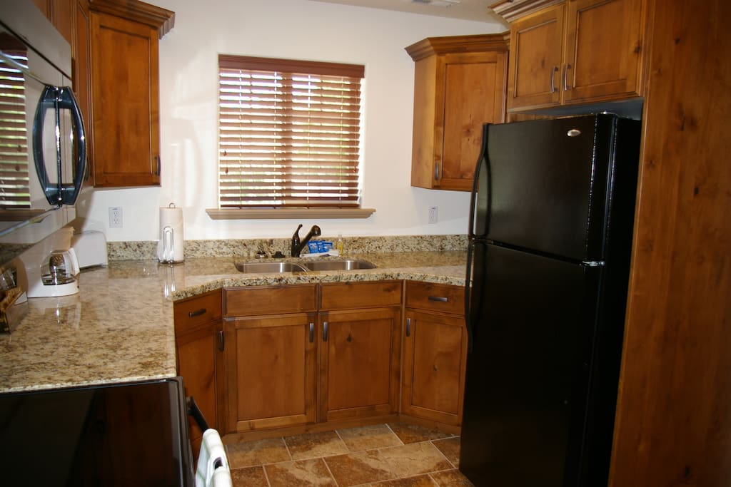 Large kitchen with granite countertops, fridge, cooktop, oven, and microwave. Includes all cookware and place settings you'll need.
