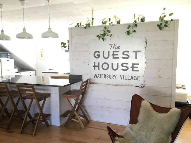 """""""The Guest House"""" historic sign is prominently displayed within the loft."""