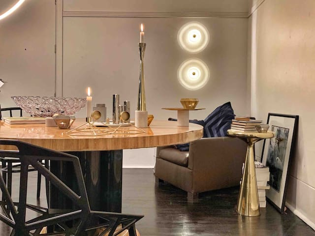 A unique regency-style dining table sits at the centre of the living room. It is flanked by chairs from Moooi and Magis, as well as a supremely comfortable leather armchair by Minotti. The brass side table and lights are by Tom Dixon.