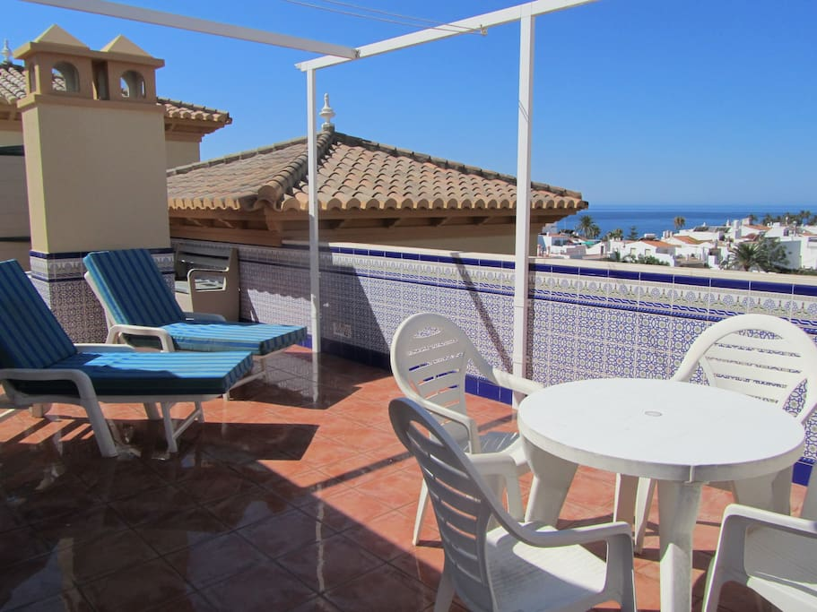 Private roof terrace with sun loungers, tables, chairs, barbecue, sea and mountain views