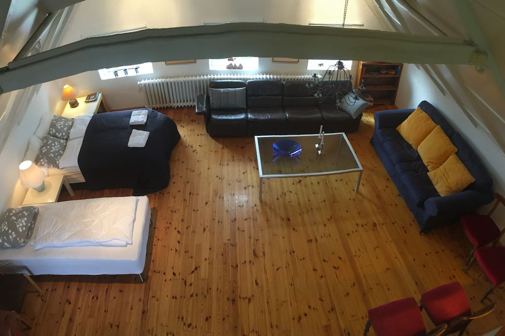 A view of the second floor space which features a queen sized bed and a living room space.