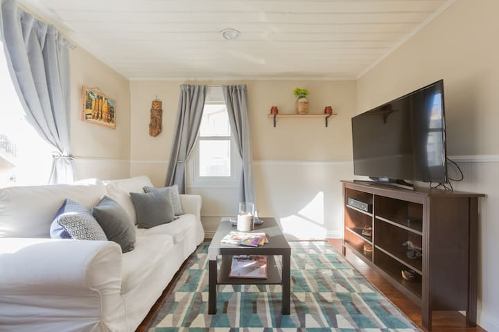"""Living room w/ 50"""" Smart TV (and cable), pull out sofa bed, & lots of magazines."""