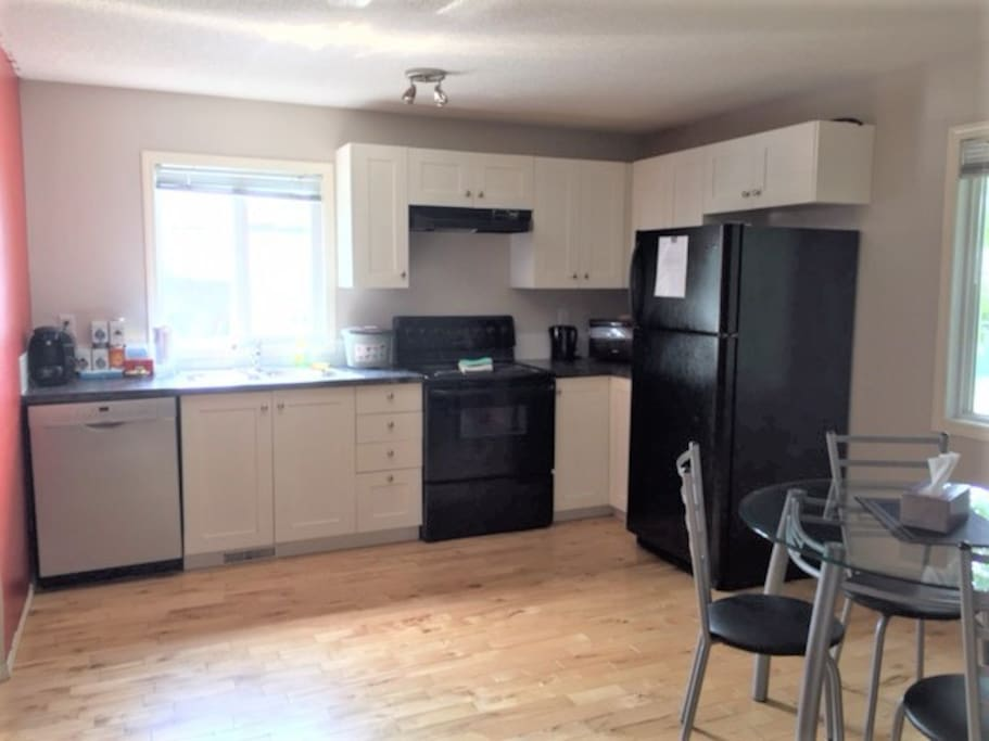 Kitchen with additional mini toaster oven, dishwasher, microwave, Tassimo coffee machine and all cooking accessories needed to prepare a meal.