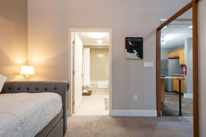 The bathroom is located just by the day-bed