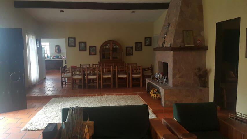Dentro de las áreas comunes de la casa, goza del enorme comedor, la sala y de la rica chimenea.