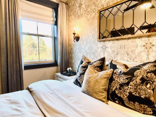 Queen Bedroom offers a cozy retreat with blackout roman shades, velvet drapery, and luxury bedding on a memory foam mattress. Smart TV with swivel mount, large closet, 2 drawer side tables, under bed storage, ceiling fan, and bedside sconces.