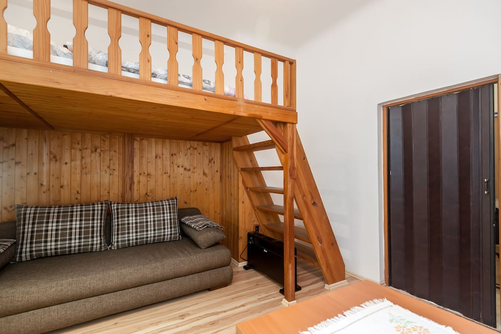 obývací pokoj s rozkládací sedačkou a patrem na spaní