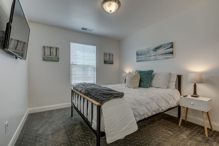 Bedroom 3 includes comfortable queen bed, smart TV and large closet with dresser.