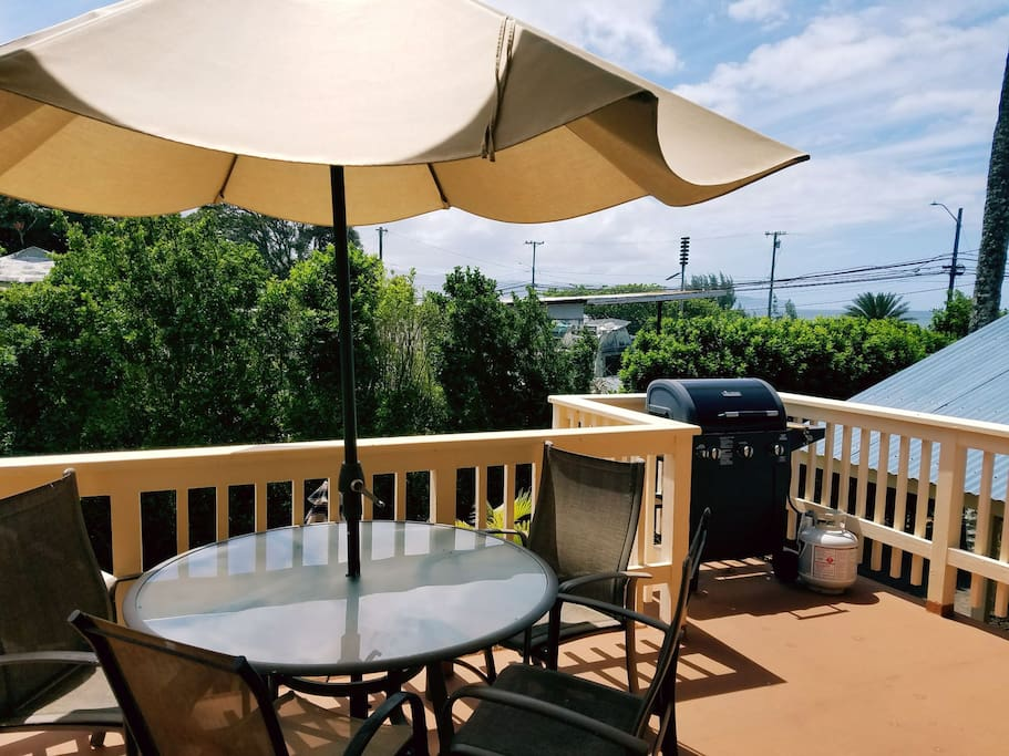 large deck with table/chairs/umbrella and BBQ