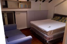SOHO office tables replaced with Queen bed and blue sofa. Wardrobes on right side partially visible.