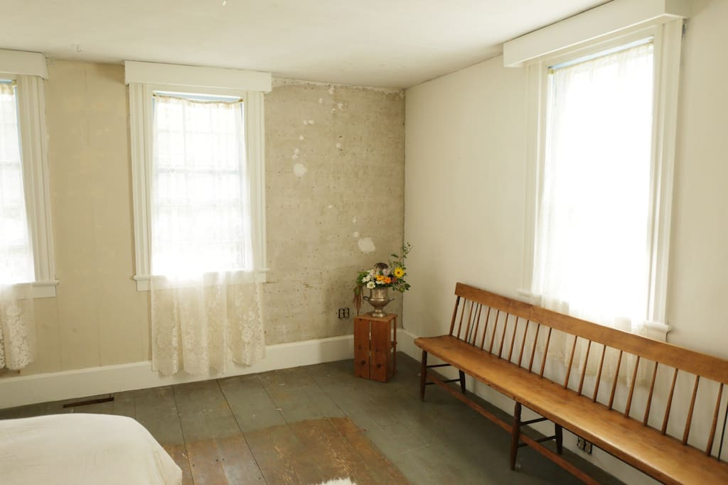 The bedroom has exposed, original horsehair plaster walls   and wood floors that extend throughout the house.
