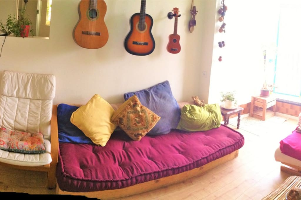 a big living-room with plenty of sofas, guitars, plants and light