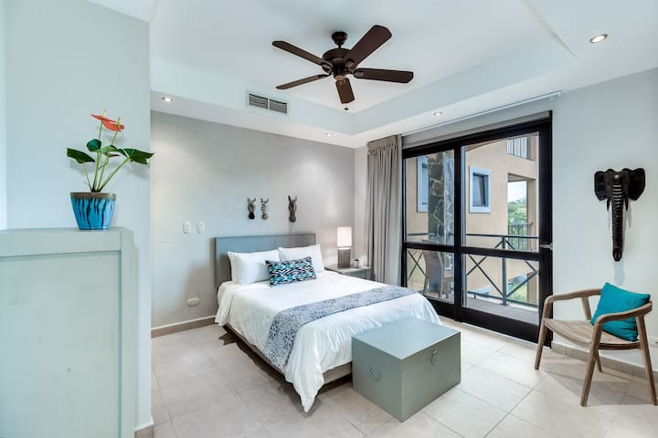 Third bedroom with queen bed and balcony access.