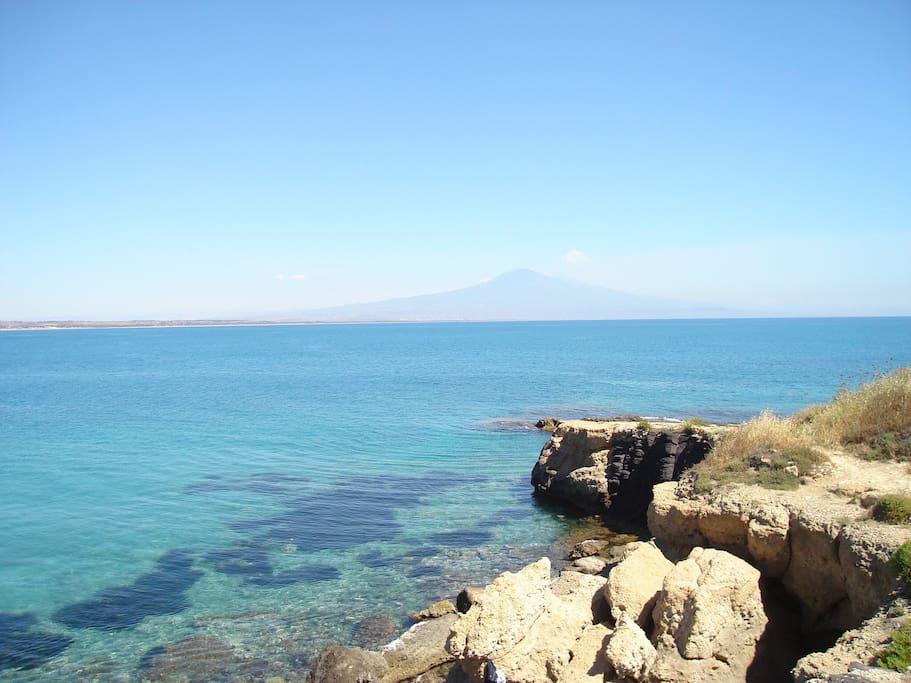 The beautiful sight of the mount Etna and the Catania's gulf from the rocky beach.
