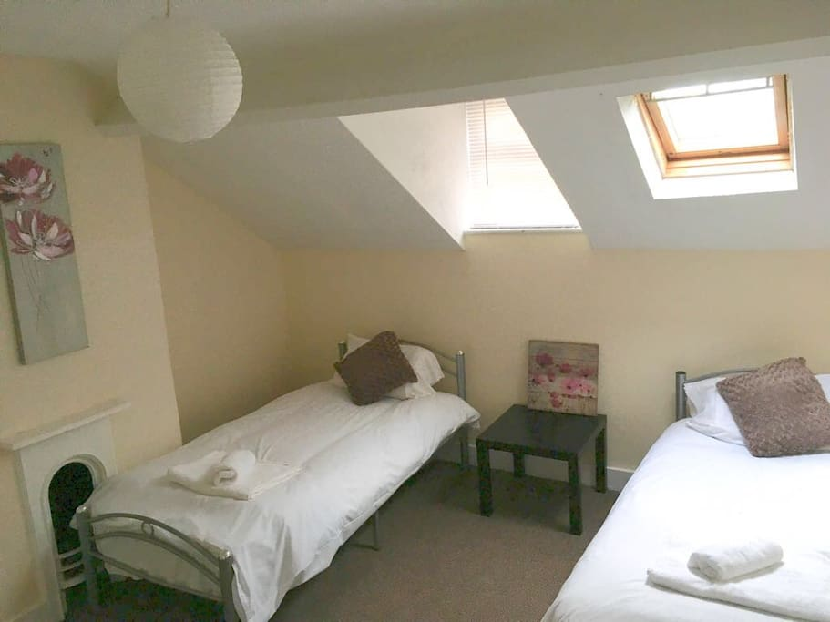 Large attic bedroom with 2 single beds & wardrobe
