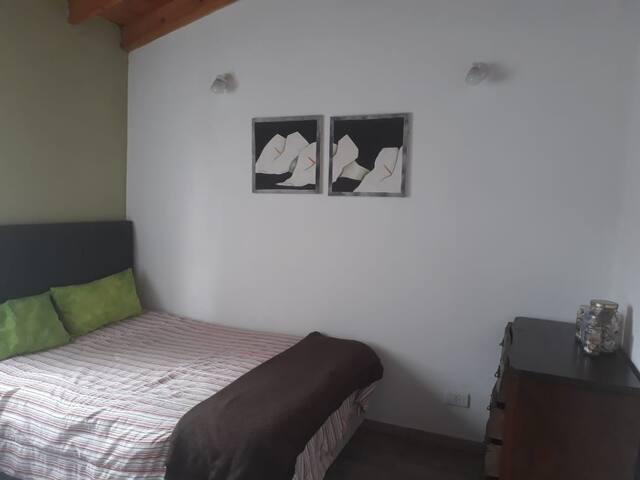 El cuarto principal es amplio, luminoso, y tiene una cama individual extra.