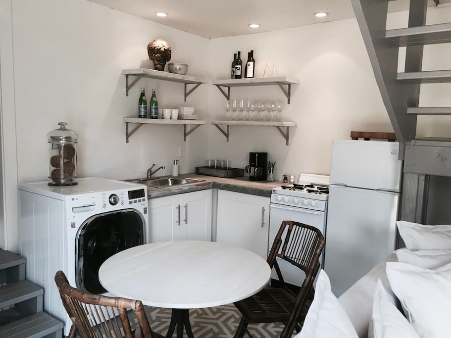 A petite chef's kitchen offers custom concrete countertops and brand-new appliances, including a gas-top stove, refrigerator, and an LG washer/dryer.