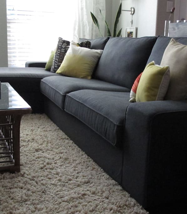Comfy couch in living room with large flat screen with cable