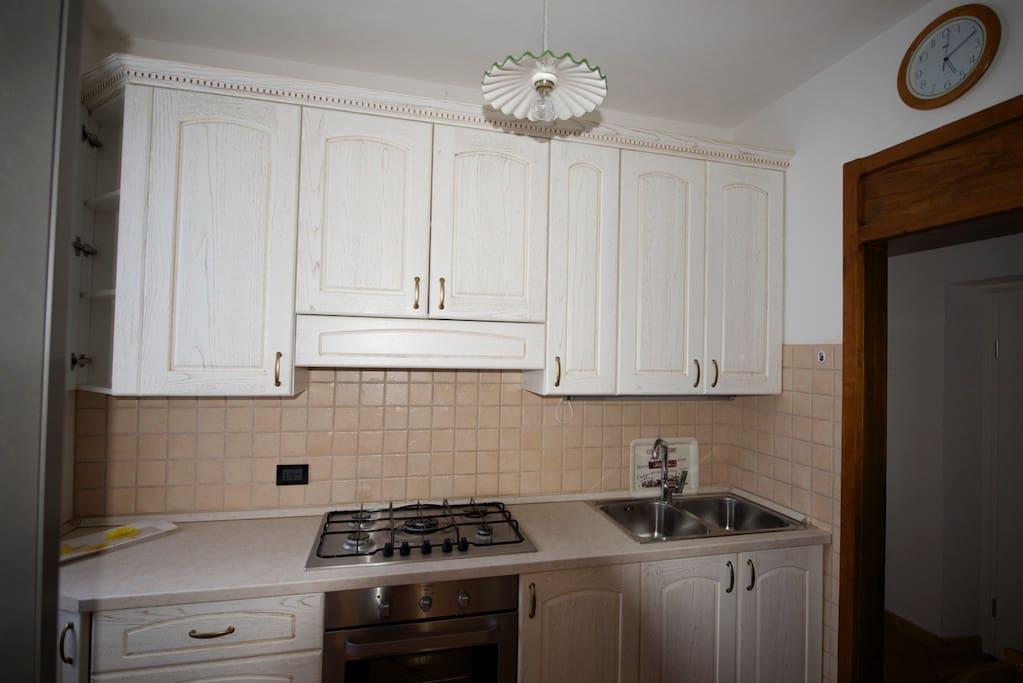 La cucina, nuova e con mobili in legno bianco