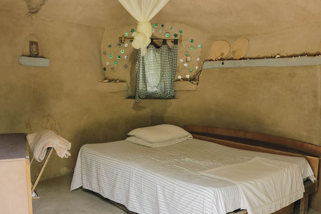 The space has a full bed, mosquito net, and fan. There is a private bucket shower and bucket toilet as well as access to shared facilities.