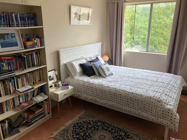 Sunny room with a queen-sized bed, a Persian rug, interesting art and a poetry collection.
