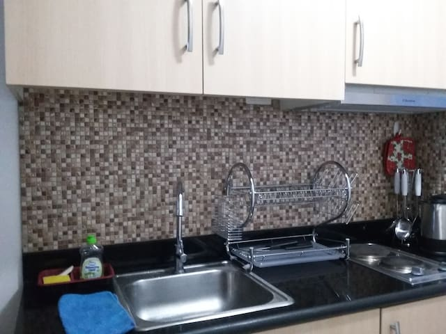 The kitchen with a beautiful backsplash, range, cooking utensils and a microwave