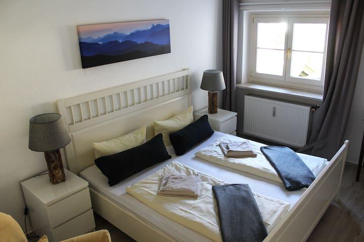 Schlafzimmer mit Doppelbett und Arbeitsplatz