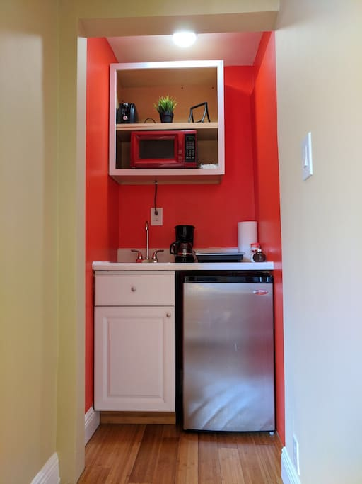 A one burner kitchenette with utensils to cook, coffee maker, refrigerator, microwave and toaster.