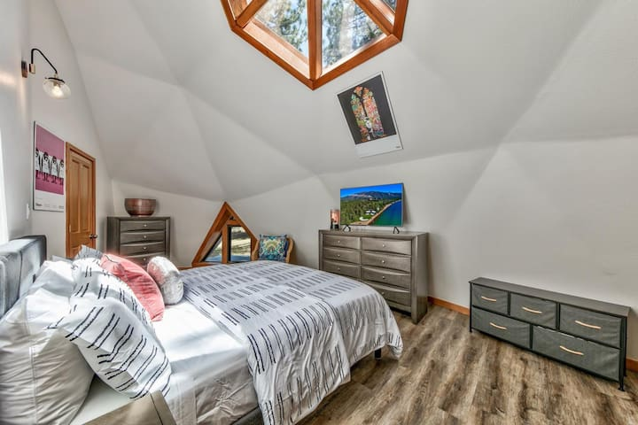 The Primary bedroom is upstairs with a king bed, HDTV, uncovered skylights, and a private entrance to the upstairs bathroom.
