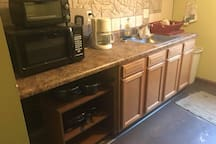 microwave, coffee pot, pots, pans, sink, toaster oven