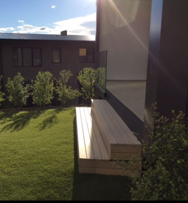 Deck leading down to artificial grass.