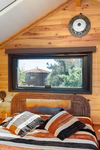Dormitorio vistas al jardin y la casa barril.