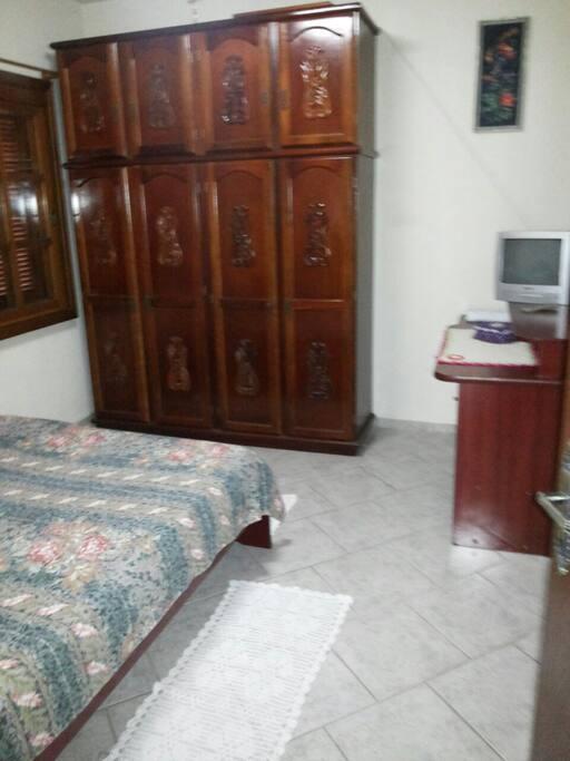 Quarto com cama de casal,  roupeiro, escrivaninha, cadeira e uma televisão.
