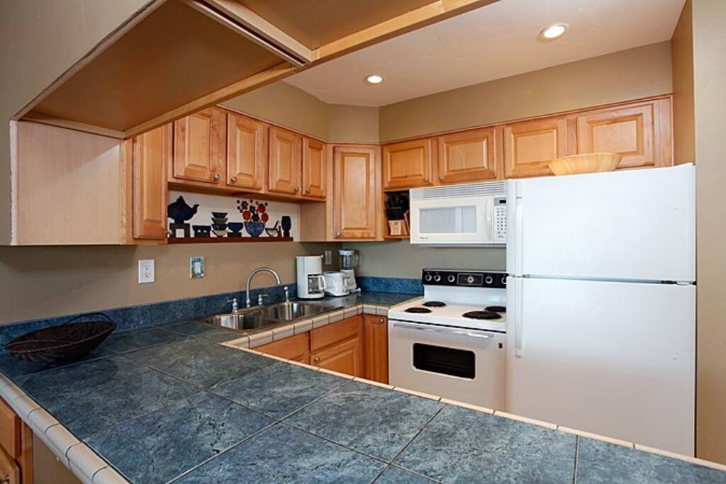 Beautiful newly remodeled kitchen with gorgeous tiled counter tops and full sized appliances.