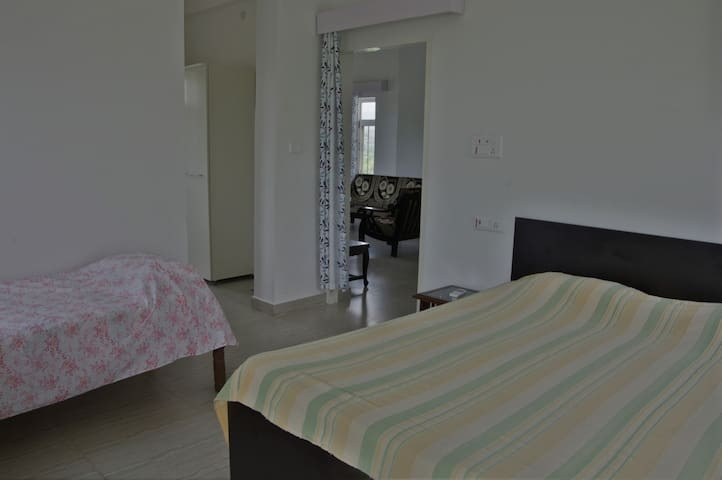 Spacious airconditioned bedroom can accommodate up to 4 beds - One king size Godrej Interio double bed and two single beds.